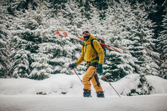 Young man with ski walking in the snow forest. Young man with ski walking in the snowy winter forest Royalty Free Stock Images