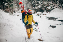 Young man with ski walking in the snowy forest. Young man with ski walking in the snowy winter forest Royalty Free Stock Images