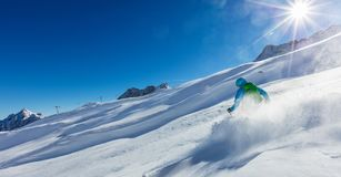 Young man skier running downhill in powder snow Royalty Free Stock Image