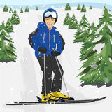 Young man skier standing on snowy ski slope with trees Stock Image