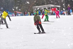 Young man on skiing downhill with people in the background, snow stock images