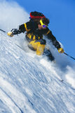 Young man skiing powder snow in mountains in winte Royalty Free Stock Images
