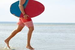 Young man with skimboard on summer beach Royalty Free Stock Image