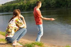 Young man skimming stones across water Royalty Free Stock Photography