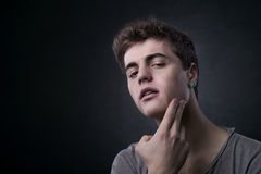 Young man skincare. Young man touching his face skin and checking for blemishes Royalty Free Stock Photos