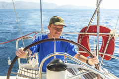 Young man skipper at the helm controls sailing yacht. Sport. Stock Photos