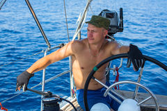 Young man skipper of a sailing yacht. Luxury vacation. Royalty Free Stock Image