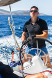 Young man skipper steers wheel sailing yacht boat. Stock Image