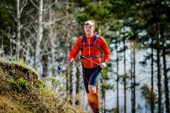 Young man skyrunning running with walking sticks in hands Stock Photos