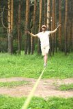 young man is slacklining walking and balancing on a rope, slackline outdoors Stock Images