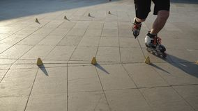 Close-up legs of a young man is professionally skating between cones on a nice evening sunset in a city park. Freestyle. Young man slalom skater is dancing stock video footage