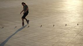 Young long-haired man roller skater is dancing between cones in a nice evening in a city park. Freestyle slalom Roller. Young man slalom skater is dancing stock video footage