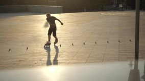 Young long-haired bearded man roller skater is dancing between cones in the evening in a city park at sunset. Freestyle. Young man slalom skater is dancing stock footage
