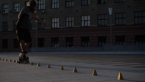 Young long-haired man roller skater is dancing between cones in the evening in a city square at sunset. Freestyle slalom. Young man slalom skater is dancing stock footage