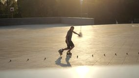 Young long-haired man roller skater is dancing between cones in the evening in a city park at sunset. Freestyle slalom. Young man slalom skater is dancing stock video footage