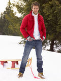 Young Man With Sled In Alpine Snow Scene Stock Photography