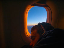 Young man sleep in the airplane. At sunrise Stock Photo