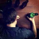 Young Man sleep with a Beer. Toned Photo of Tired Man sleep with Bottle of the Beer on a Table Royalty Free Stock Photos