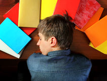 Young Man sleep on the Books. Tired Young Man sleep on the Books at the Home Royalty Free Stock Image