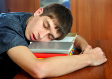 Young Man sleep on the Books. Tired Young Man sleep on the Books at the Home Royalty Free Stock Photos