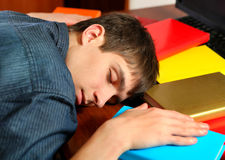 Young Man sleep on the Books. Tired Young Man sleep on the Books at the Home Stock Photos