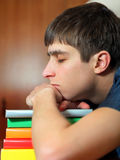 Young Man sleep on the Books. Tired Young Man sleep on the Books at the Home Stock Image