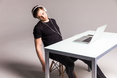 Young man sleep while wearing headphones and work on laptop on his office table on white background. work Stock Photo
