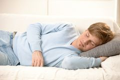 Young man sleeping. Tired young man sleeping on couch, taking afternoon nap Royalty Free Stock Photo