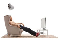 Young man sleeping in an armchair in front of a television royalty free stock photo