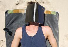 Young man sleeping on beach with book covering face Royalty Free Stock Image