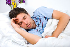 Young man sleeping in bed stock photography