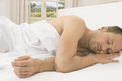 Young man sleeping in bed. Stock Image