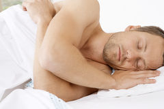 Young man sleeping in bed. Stock Images