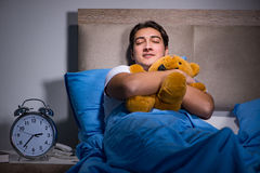 The young man sleeping in the bed Stock Images