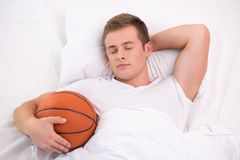 Young man sleeping in bed with basketball Stock Photos