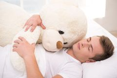 Young man sleeping in bed with big teddy bear Stock Photography