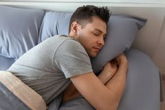 Young man sleeping in bed. At home royalty free stock image