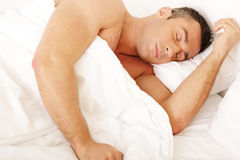 Young man sleeping on the bed Stock Photography