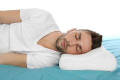 Young man sleeping on bed with orthopedic pillow. Against white background. Healthy posture concept Stock Image