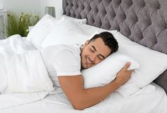 Young man sleeping in bed with soft pillows royalty free stock image