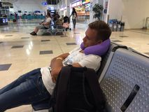 A young man is sleeping at the airport, putting a pillow under h. A young man is sleeping on a chair at the airport, putting a pillow under his head, mobile royalty free stock photo
