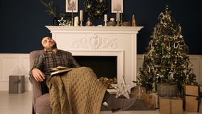 Young man sleeping in a chair on Christmas evening. Boring christmas concept. royalty free stock images
