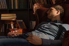 Young Man Sleeping on the Chair Holding a Book Royalty Free Stock Photos