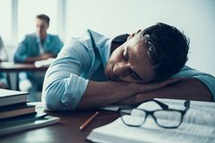 Young Student Sleeping in Classroom at College. Young Man Sleeping in Classroom at College. Education Concept. Writing on Lesson. Multiethnic Students. Sitting Stock Photography