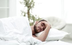 Young man is sleeping in a comfortable hotel room. Photo with copy space Royalty Free Stock Photo