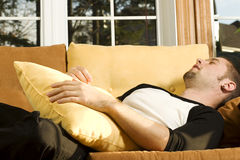 Young man sleeping on couch. In living room Royalty Free Stock Photos