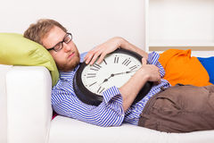 Young man sleeping on the couch with big clock Stock Photography