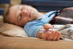 Young man sleeping on the couch with a bottle Royalty Free Stock Photography
