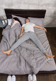 Young man sleeping in free fall position with his wife occupied. Young men sleeping in free fall position with his wife occupied the whole bed, wearing pajamas stock photo