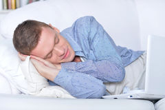 Young man sleeping in front of laptop Stock Photo